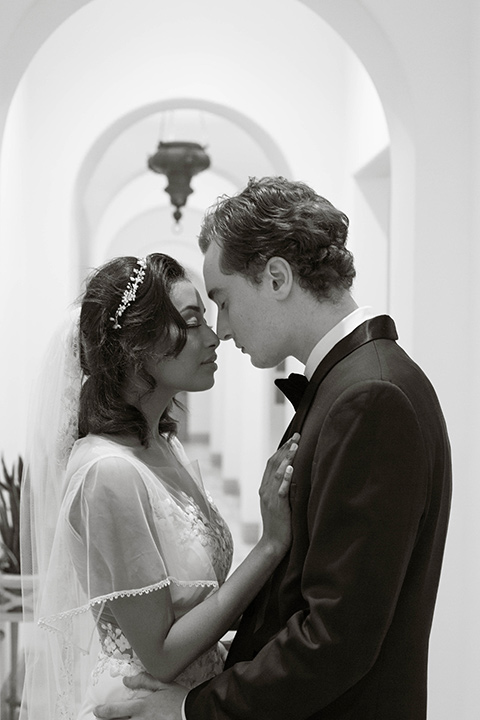 couple close groom in a navy blue tuxedo with a black bow tie and the bride in a white lace flowing gown and a long cathedral veil