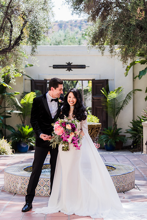 bride in a long gown with a flowing train and cape groom in a black velvet tuxedo with a black bow tie