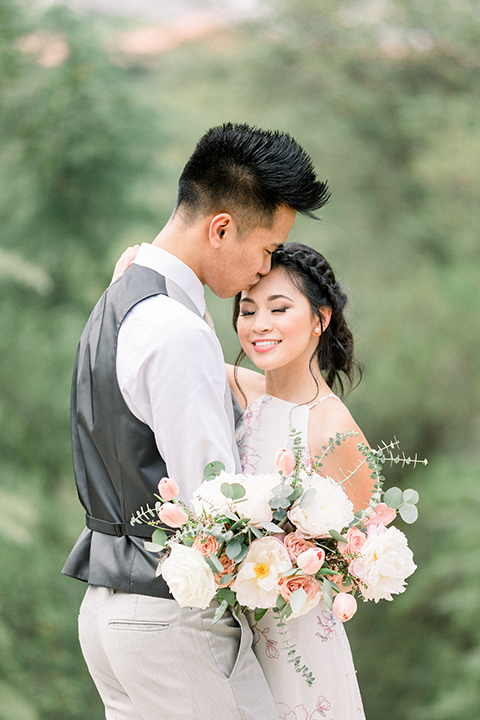 bride in a floral gown with a high neckline and a low bun hairstyle, the groom in a light grey pant and vest outfit with a white floral necktie embracing each other and smiling