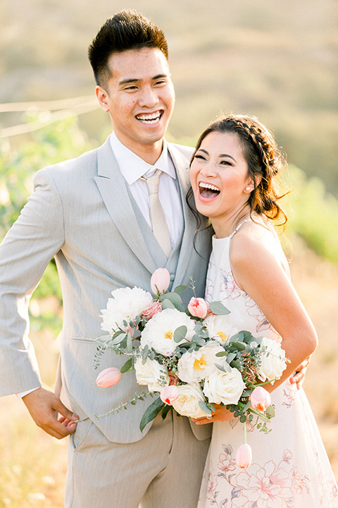 bride in a floral gown with a high neckline and a low bun hairstyle, the groom in a light grey pant and vest outfit with a white floral necktie laughing