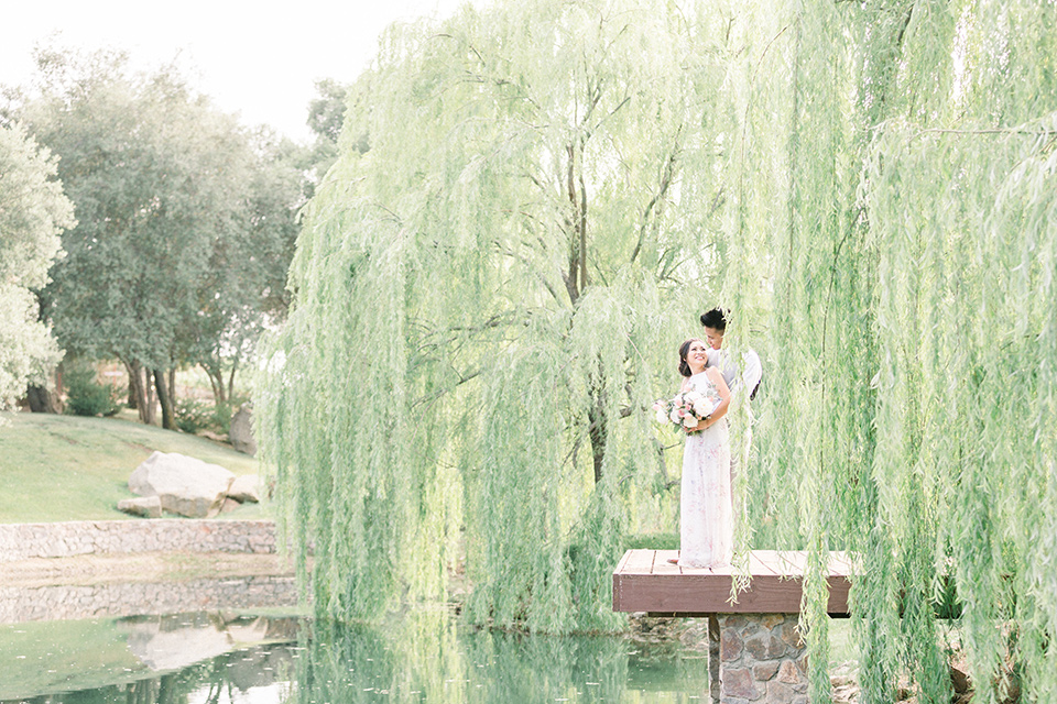 bride in a floral gown with a high neckline and a low bun hairstyle, the groom in a light grey pant and vest outfit with a white floral necktie standing on a dock underneath a willow tree