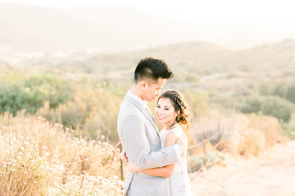 bride in a floral gown with a high neckline and a low bun hairstyle, the groom in a light grey pant and vest outfit with a white floral necktie embracing in a meadow