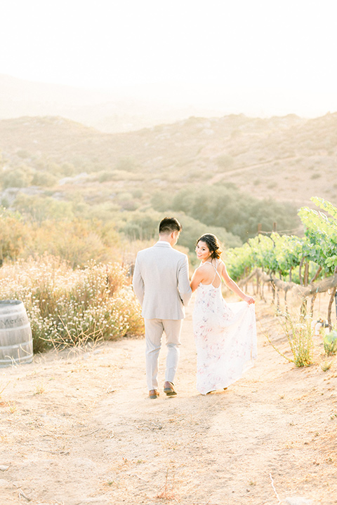 bride in a floral gown with a high neckline and a low bun hairstyle, the groom in a light grey pant and vest outfit with a white floral necktie together under the willow tree