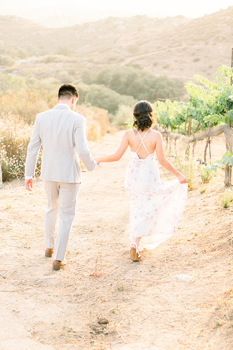 bride in a floral gown with a high neckline and a low bun hairstyle, the groom in a light grey pant and vest outfit with a white floral necktie walking away together