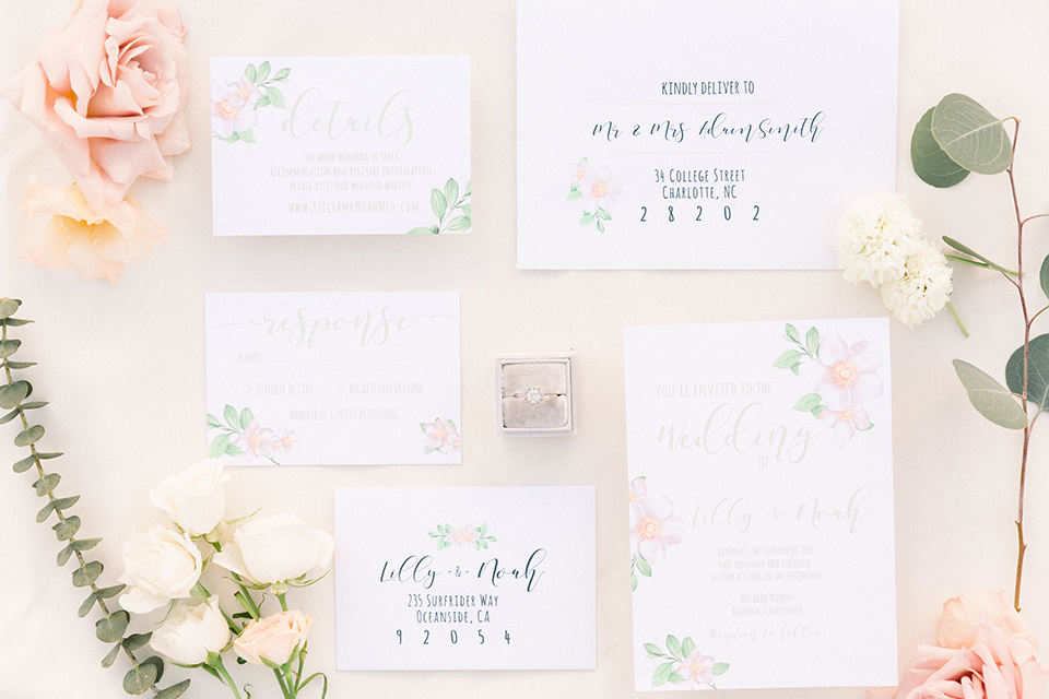 white invitations with a small floral design and calligraphy