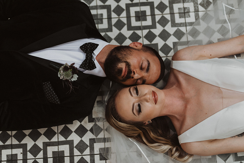 bride in a tulle a line gown with a sweetheart neckline and a crystal bodice and the groom in a black velvet tuxedo and black bow tie laying on ground