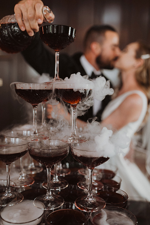 bride in a tulle a line gown with a sweetheart neckline and a crystal bodice and the groom in a black velvet tuxedo and black bow tie by champagne