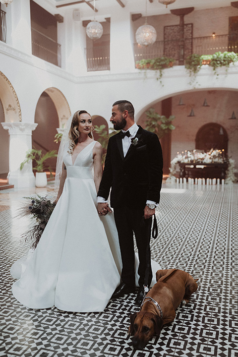bride in a tulle a line gown with a sweetheart neckline and a crystal bodice and the groom in a black velvet tuxedo and black bow tie by reception table with dog