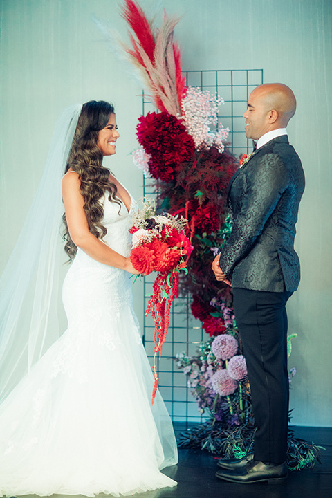 bride in a formfitting gown with a bright red lip and the groom in a black paisley tuxedo with a black bow tie