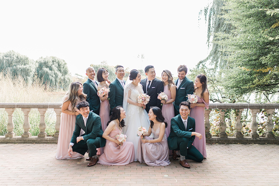 bride in a tulle ballgown with a plunging neckline and a loose bun, bridesmaids in light pink gowns, groomsmen in dark green suits and groom in a black suit with a black long tie