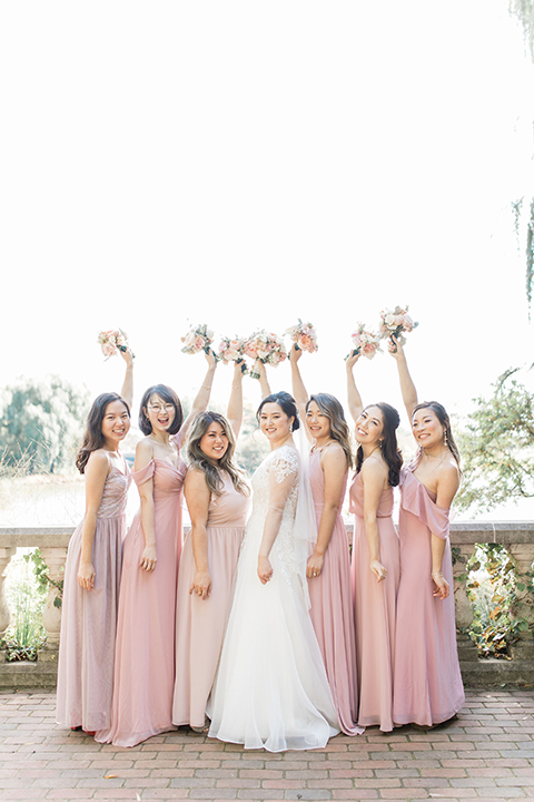 bride in a tulle ballgown with a plunging neckline and a loose bun and bridesmaids in pink gowns
