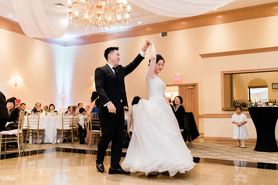 bride in a tulle ballgown with a plunging neckline and a loose bun and groom in a black suit with a black long tie