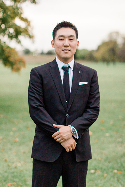 groom in a black suit with a long tie