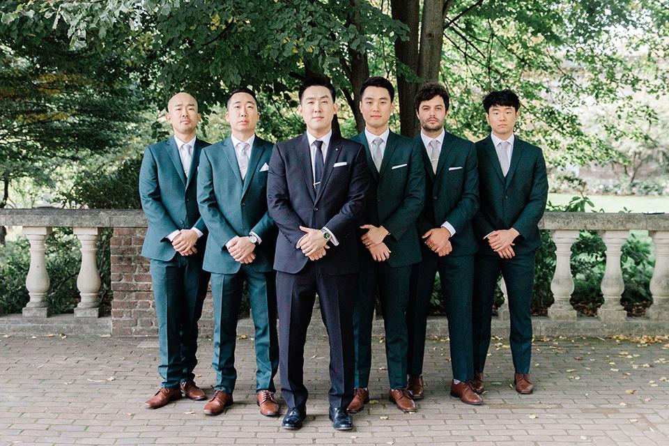 groomsmen in dark green suits and groom in a black suit with a black long tie
