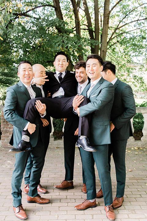 groom in a black suit with a long tie groomsmen in dark black suits