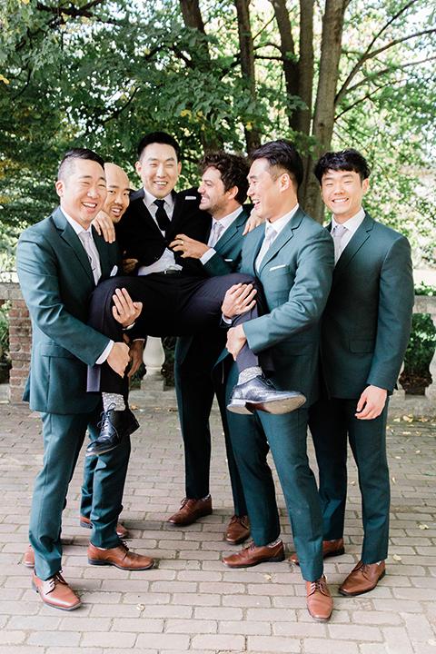 groom in a black suit and long tie, groomsmen in dark green suits