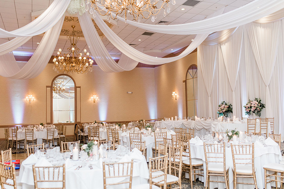 white tables with simple calligraphy table numbers with white linens draping the ceiling
