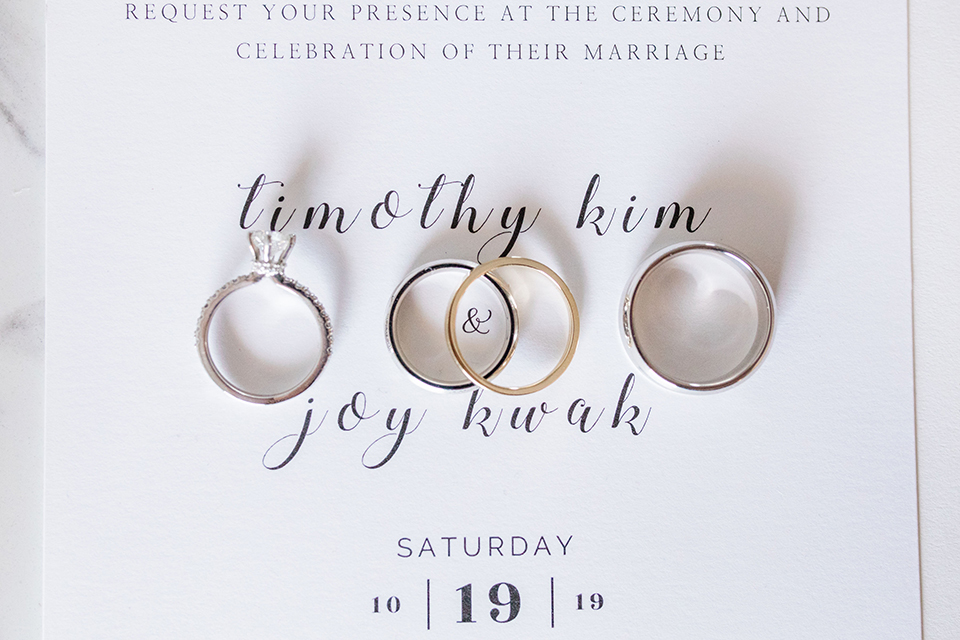 white invitations and rings