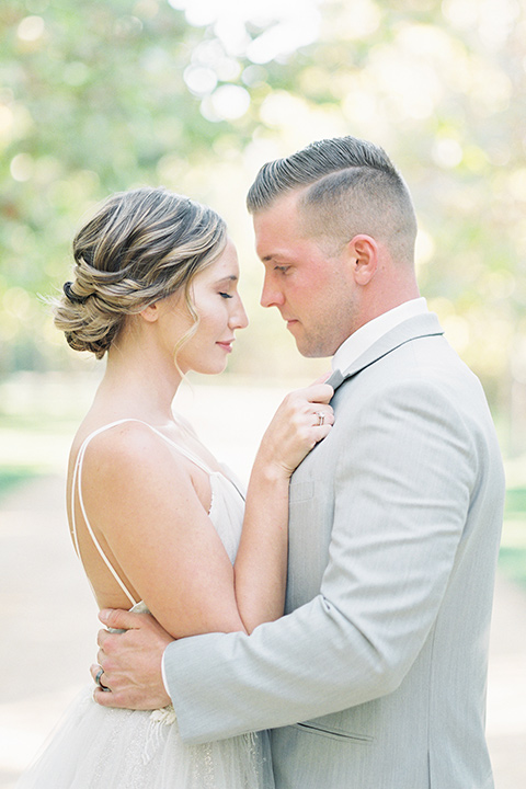 bride in a blush ballgown with thin straps and the groom in a grey suit with a white long tie