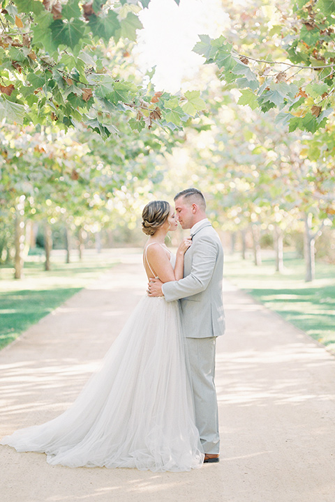 bride in a blush tulle ballgown with thin straps and hair up in a loose bun and the groom in a light grey suit with a white tie