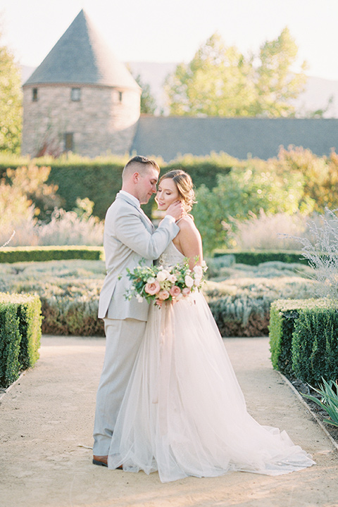 bride in a blush ballgown with thin straps and the groom in a grey suit with a white long tie embracing