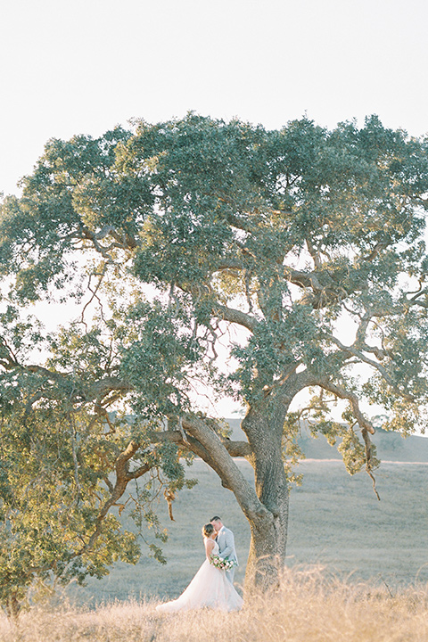bride in a blush tulle ballgown with thin straps and hair up in a loose bun and the groom in a light grey suit with a white tie under the tree