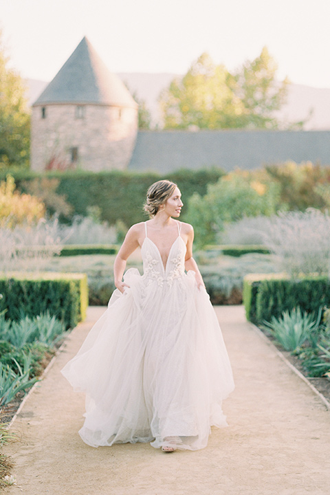 bride in a blush tulle ballgown with thin straps and hair up in a loose bun