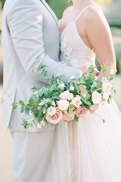 bride in a blush tulle ballgown with thin straps and hair up in a loose bun and the groom in a light grey suit with a white tie holding each other close