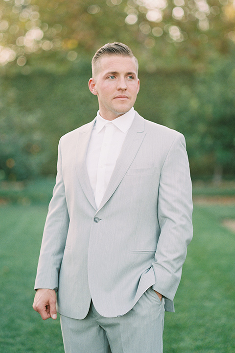groom in a light grey suit with a white tie