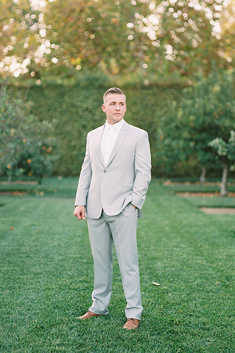 groom in a grey suit with a white long tie