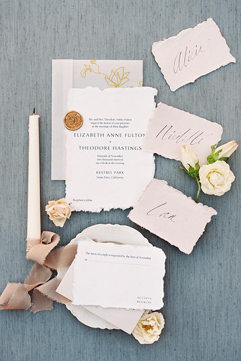 white invitations with blush flowers and calligraphy