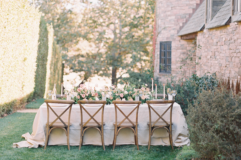 wooden table with white linens and farm table chairs