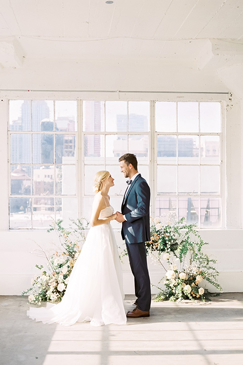 bride in a flowing modern tulle gown and the groom in a slate blue suit with grey velvet bow tie