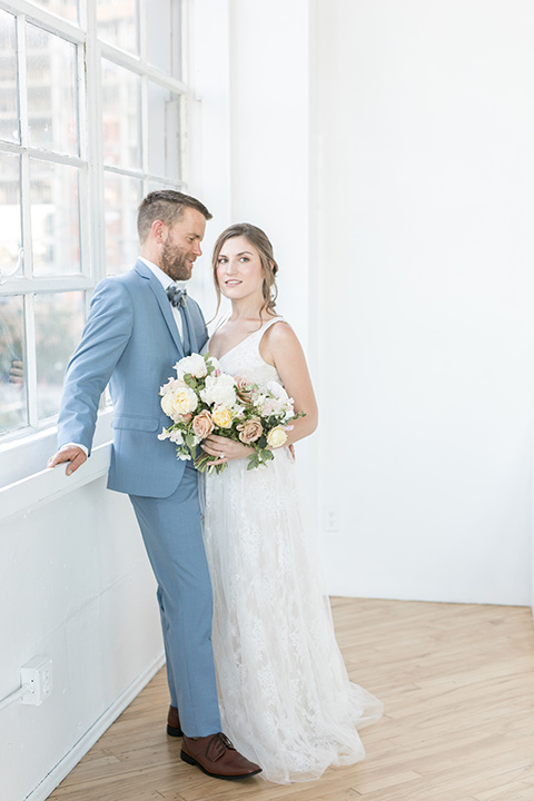 bride and groom by the windows, the bride in a flowing white gown with a lace detailing and straps.  The groom in a light blue suit with a grey velvet bow tie
