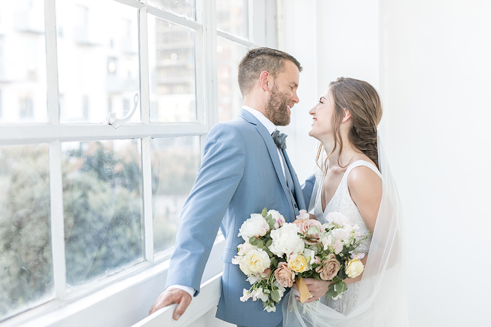 bride and groom by the windows looking at each other, the bride in a flowing white gown with a lace detailing and straps.  The groom in a light blue suit with a grey velvet bow tie