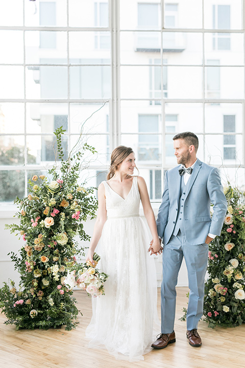 bride and groom at the ceremony, the bride in a flowing white gown with a lace detailing and straps.  The groom in a light blue suit with a grey velvet bow tie