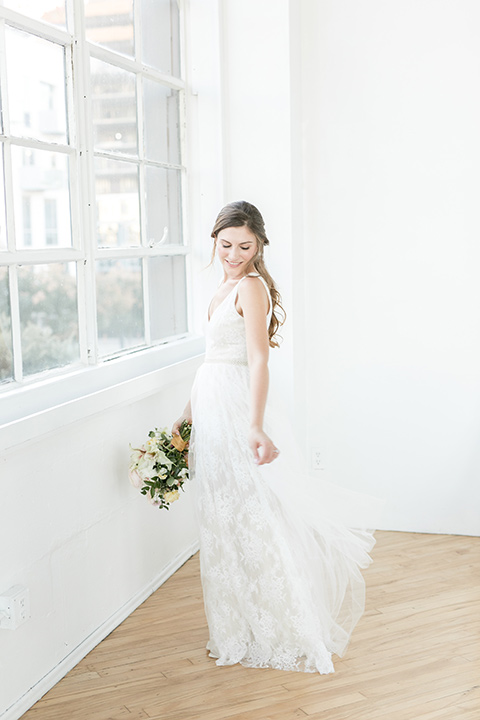 bride by the windows, wearing a flowing white gown with a lace detailing and straps