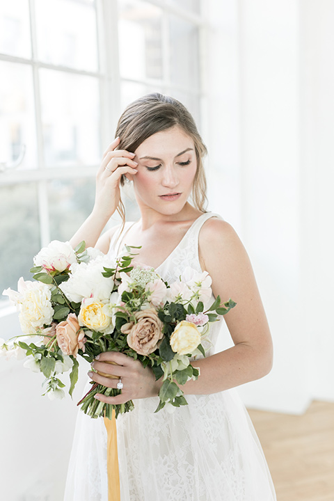bride holding the flower bouquet in a flowing white gown with a lace detailing and straps
