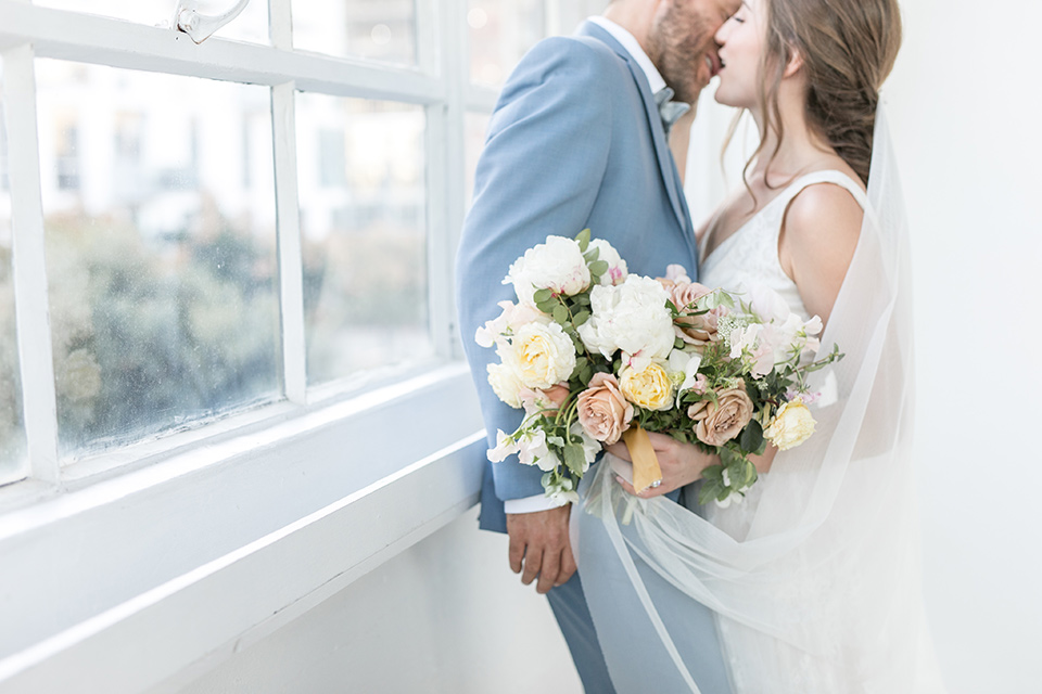 bride and groom by the windows looking at each other up close, the bride in a flowing white gown with a lace detailing and straps.  The groom in a light blue suit with a grey velvet bow tie