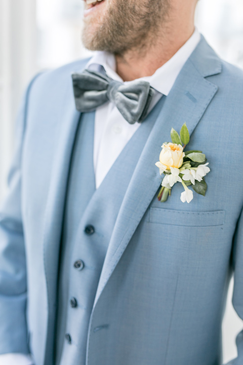 groom attire close up, the groom in a light blue suit with a grey velvet bow tie