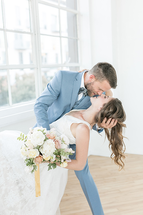 groom dipping the bride, the bride in a flowing white gown with a lace detailing and straps.  The groom in a light blue suit with a grey velvet bow tie