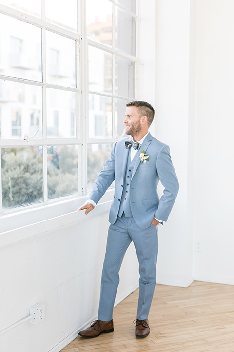 groom by the windows, the groom in a light blue suit with a grey velvet bow tie