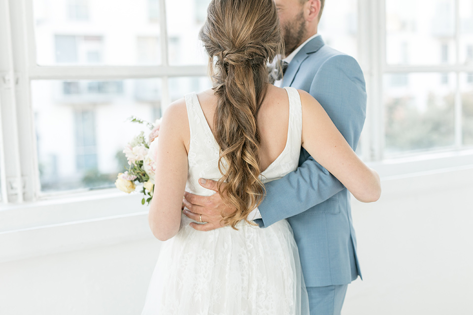 groom holding the bride and spinning her around, the bride in a flowing white gown with a lace detailing and straps.  The groom in a light blue suit with a grey velvet bow tie
