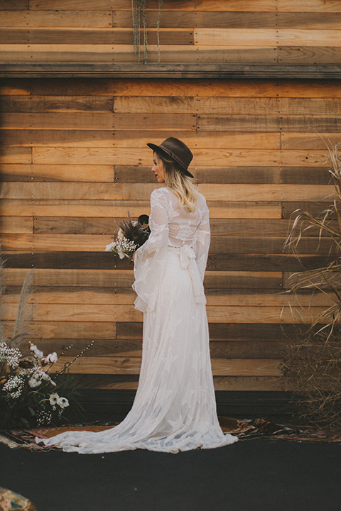 bride in a lace bohemian style gown with long flowing sleeves and a wide brimmed hat