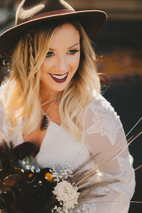 bride in a lace bohemian style gown with long sleeves and a wide brimmed hat