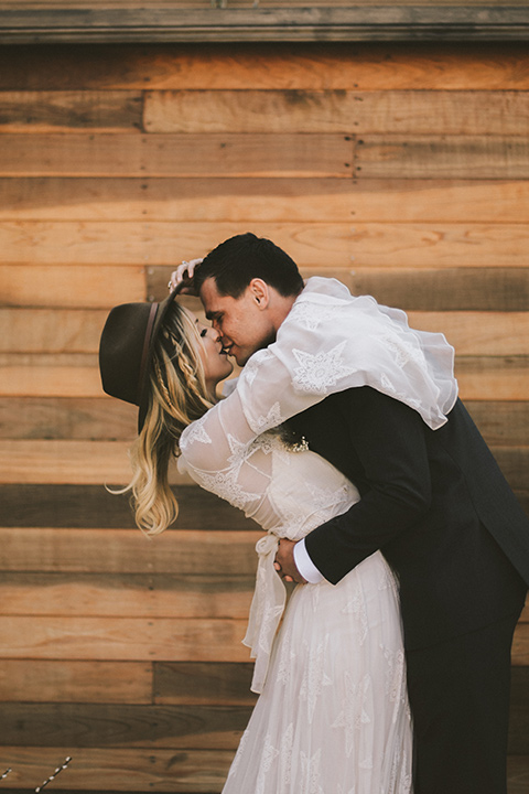 bride in a lace bohemian style gown with long flowing sleeves and a wide brimmed hat groom in a dark grey notch lapel suit with a black bow tie
