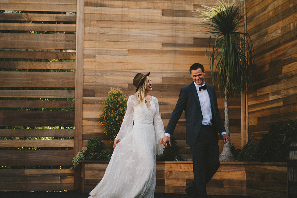 white lace gown with long billowing sleeves and a wide brimmed hat and the groom in a dark grey notch lapel suit and a black bow tie walking through venue