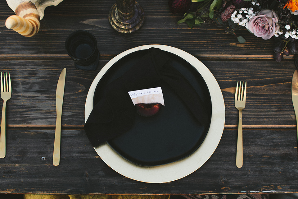 bohemian wooden table with big full flower décor with burgundy details and black and gold flatware and linens