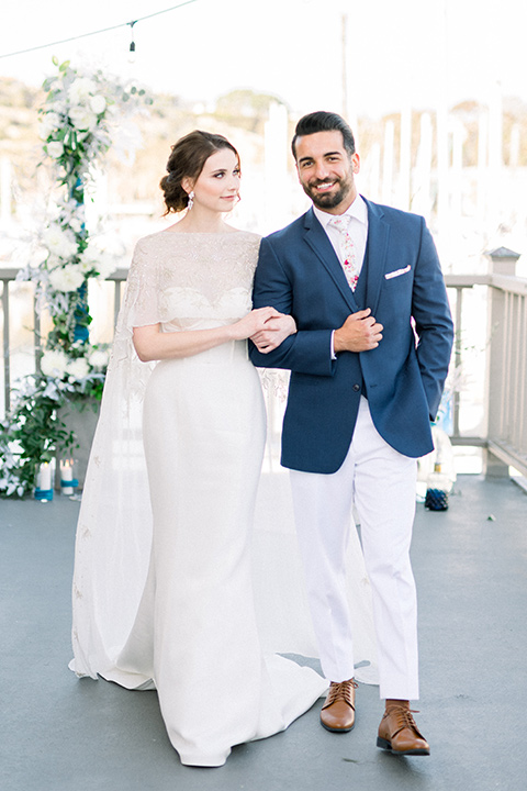 bride-in-a-flowing-gown-with-a-crystal-bodice-and-hair-in-a-loose-bun and the groom in a blue suit jacket with white pants and a floral long tie