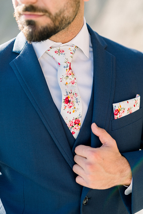 the groom in a blue suit jacket with white pants and a floral long tie